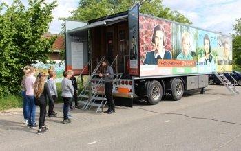 Kinderen worden voor de trailer ontvangen door een museumdocent.