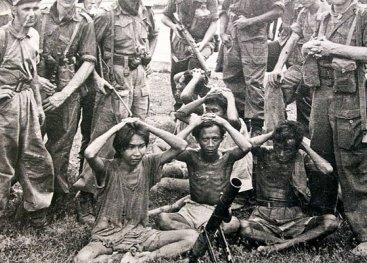 Nederlandse soldaten richten nonchalant hun wapens op soldaten van het Indonesische regeringsleger die zich hebben overgegeven. Solo, Midden-Java, 21 december 1948.