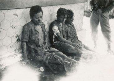 Drie Indonesische gevangenen worden bewaakt door een Nederlandse militair. Java, 27 november 1947.