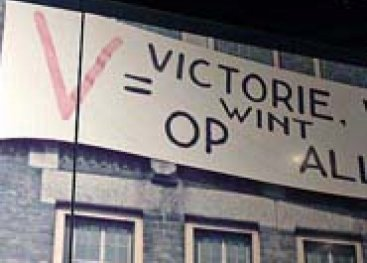 Detail van een wand in het museum, met de leus V is victorie want Duitsland wint op alle fronten